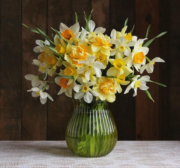 Blumenstrauß von gelben narzissen in einem glasvase auf einem hölzernen hintergrund.