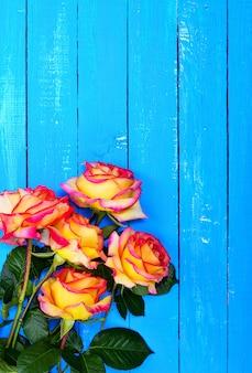 Blumenstrauß von gelben rosen auf einem blauen hölzernen hintergrund