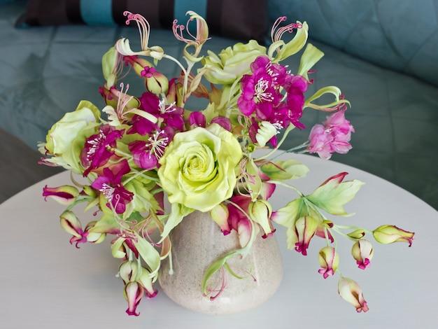 Blumenstrauß von gelben rosen mit roten blumen mit den knospen in einem vase auf einer weißen tabelle