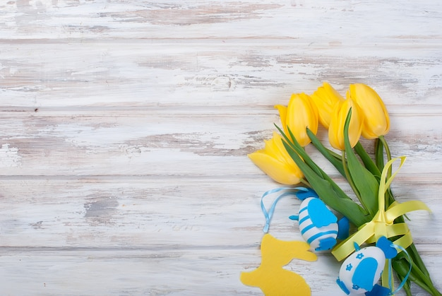Blumenstrauß von gelben tulpen und von chikken ostereiern mit einem blauen band auf einem holz