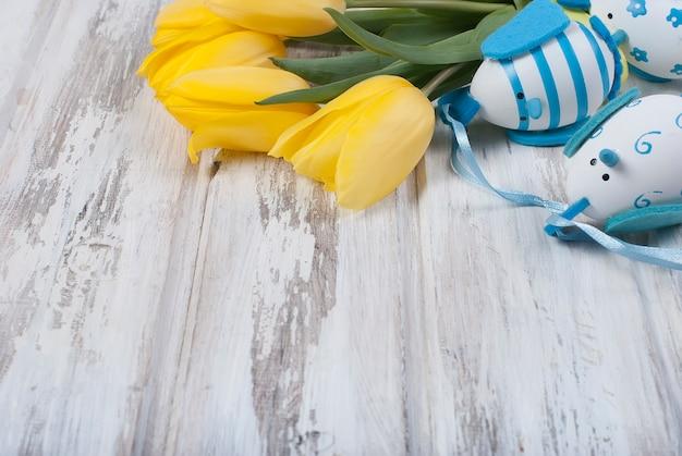 Blumenstrauß von gelben tulpen und von chikken ostereiern mit einem blauen band auf woodenon