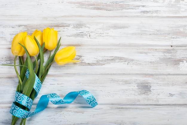 Blumenstrauß von gelben tulpen und von geschenk mit einem blauen band auf einem hölzernen hintergrund