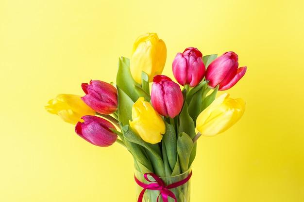 Blumenstrauß von gelben und rosa tulpen auf gelb