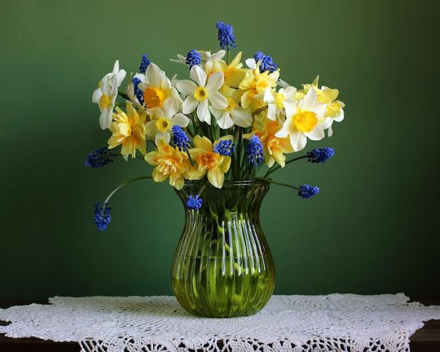 Blumenstrauß von gelben und weißen narzissen in einem vase auf einer tabelle mit einer spitzetischdecke.