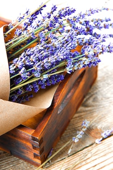 Blumenstrauß von getrocknetem lavendel in kraftpapier in einer vertikalen fotografie der holzkiste nah oben