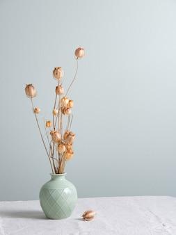 Blumenstrauß von getrockneten blumenmohnblumen in einer grünen vase auf einer leinentischdecke auf hellgrünem hintergrund. vorderansicht und kopierraum