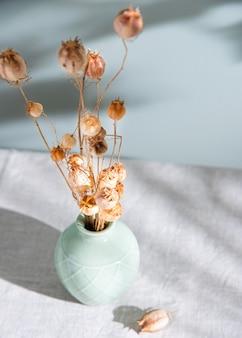 Blumenstrauß von getrockneten blumenmohnblumen in einer grünen vase auf einer leinentischdecke und morgenschatten auf hellgrünem hintergrund. nahansicht