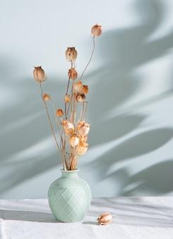 Blumenstrauß von getrockneten blumenmohnblumen in einer grünen vase auf einer leinentischdecke und morgenschatten auf pastellgrünem hintergrund. vorderansicht und kopierraum