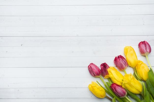 Blumenstrauß von hellen gelben und rosa tulpen auf einem leuchtpult