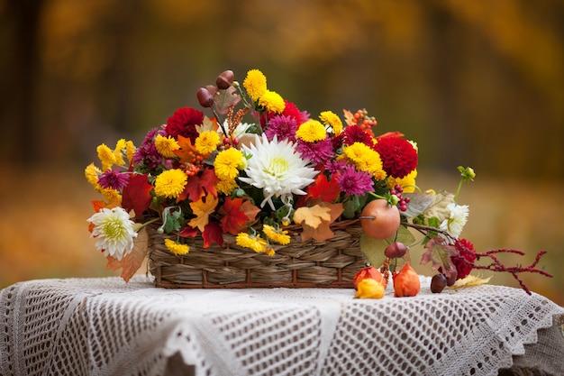 Blumenstrauß von herbstblumen im korb auf dem tisch in der rustikalen art. herbstzeit.