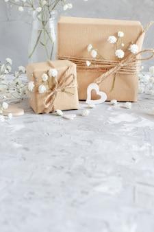 Blumenstrauß von kleinen weißen blumen und holzherzen auf einem grauen hintergrund