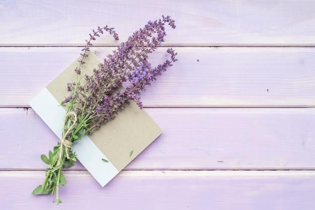 Blumenstrauß von lavendel blüht auf geschlossenem notizbuch über dem purpurroten hintergrund