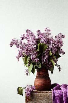 Blumenstrauß von lila blumen in einem keramiktopf auf einem alten kasten