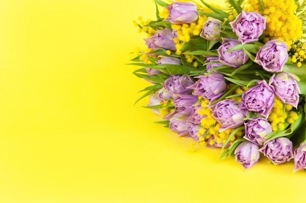 Blumenstrauß von lila tulpen und gelben mimosen auf gelbem hintergrund, kopienraum, seitenansicht, nahaufnahme.