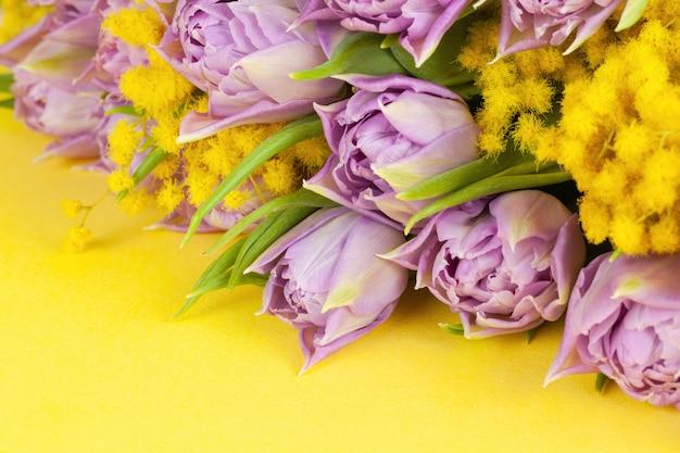 Blumenstrauß von lila tulpen und gelben mimosen auf gelbem oberflächenkopierraum, seitenansicht, nahaufnahme.
