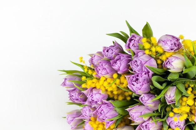 Blumenstrauß von lila tulpen und gelben mimosen auf weißem oberflächenkopierraum, seitenansicht, nahaufnahme.