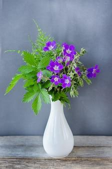 Blumenstrauß von lila wildblumen in einer weißen vase auf einem tisch auf einer grauen wand
