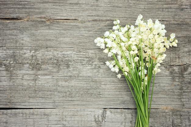 Blumenstrauß von maiglöckchen auf einem hölzernen hintergrund.