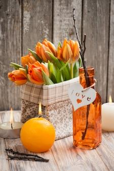 Blumenstrauß von orange tulpen, brennende kerzen