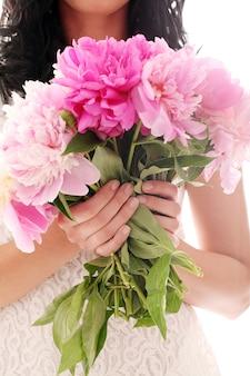 Blumenstrauß von pfingstrosen in den händen der frau