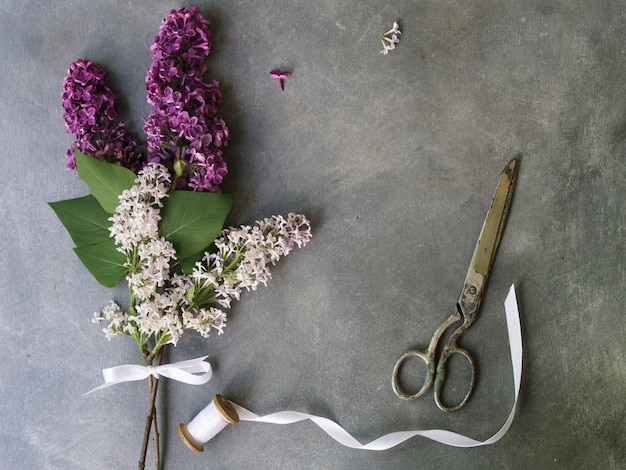 Blumenstrauß von purpurroten fliedern blüht auf einem grauen hintergrund. vintage floral hintergrund. platz kopieren