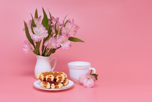 Blumenstrauß von rosa blumen auf einem rosa hintergrund. eine tasse kaffee mit milch und hausgemachten waffeln.