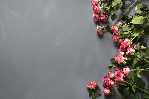 Blumenstrauß von rosa buschrosen auf grau