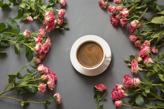 Blumenstrauß von rosa buschrosen und von tasse kaffee