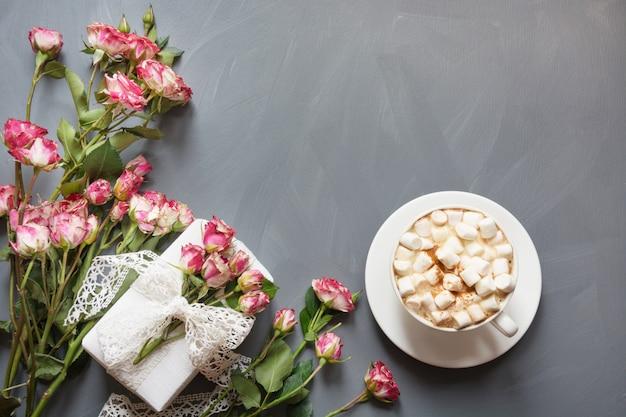 Blumenstrauß von rosa buschrosen, von weiblichem geschenk und von tasse kaffee