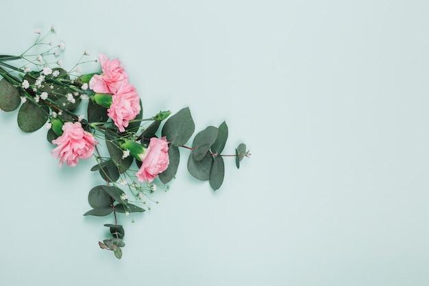 Blumenstrauß von rosa gartennelken und von gypsophila blühen auf blauem hintergrund