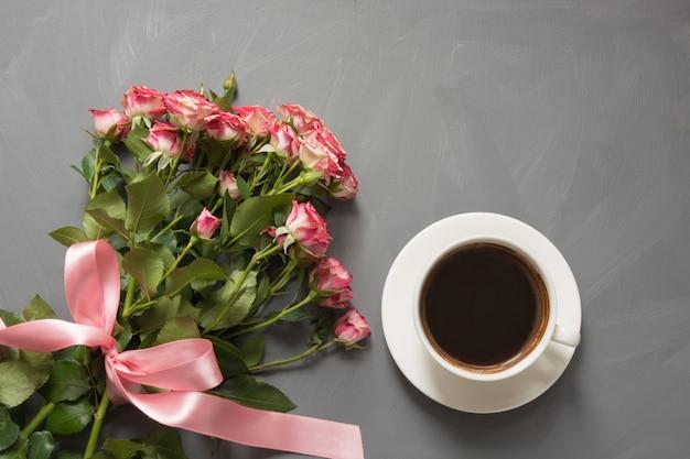 Blumenstrauß von rosa rosen und von tasse kaffee auf grau