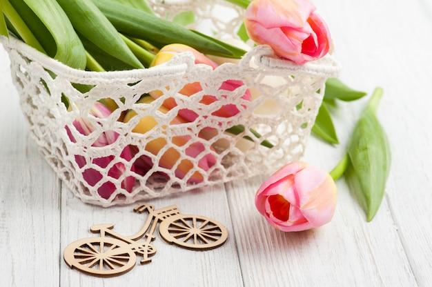 Blumenstrauß von rosa tulpen im häkelarbeitkorb