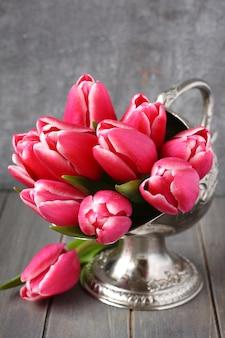 Blumenstrauß von rosa tulpen im metallvase auf hölzernem hintergrund