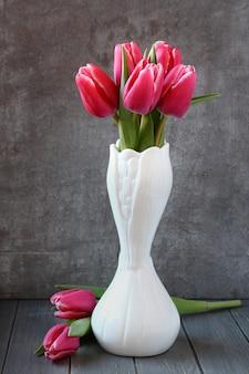 Blumenstrauß von rosa tulpen im weißen vase auf hölzernem hintergrund