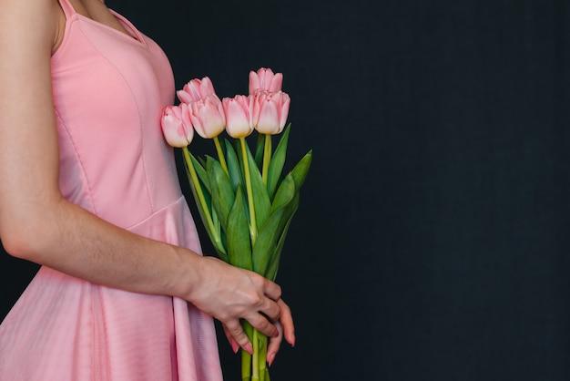 Blumenstrauß von rosa tulpen in den händen der frauen