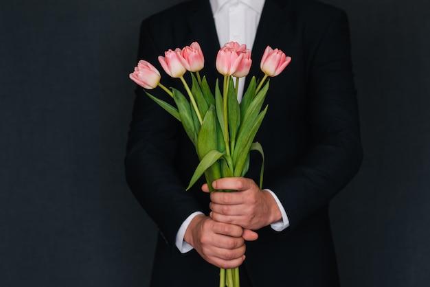 Blumenstrauß von rosa tulpen in den händen der männer in einem blauen anzug