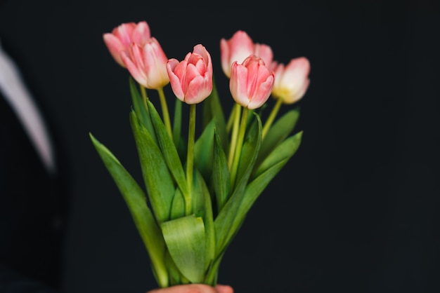 Blumenstrauß von rosa tulpen in den händen der männer