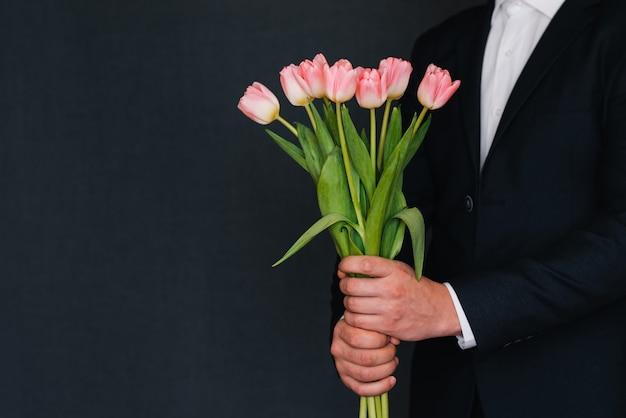 Blumenstrauß von rosa tulpen in den händen eines mannes