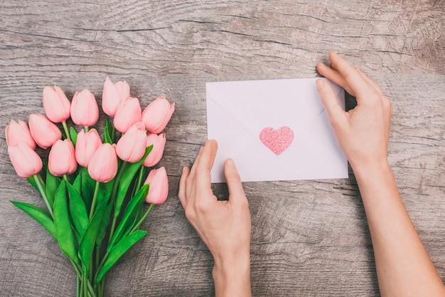 Blumenstrauß von rosa tulpen und frauenhänden halten einen leeren umschlag mit einem herzen, auf einem hölzernen hintergrund.