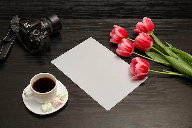 Blumenstrauß von rosa tulpen, von tasse kaffee, von dslr kamera und von blatt papier auf einem schwarzen holz