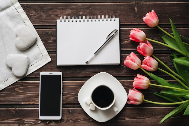 Blumenstrauß von rosa tulpenblumen mit einem tasse kaffee und einem süßen lebkuchen zum das morgen frühstück