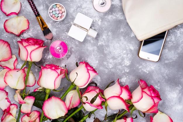 Blumenstrauß von rosen mit kosmetik im parfüm auf einem grauen hintergrund mit kopienraum