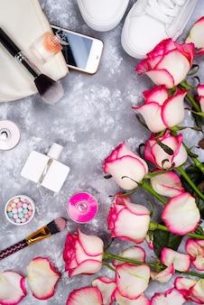 Blumenstrauß von rosen mit kosmetik im parfüm, im telefon und in den turnschuhen auf einem grauen hintergrund