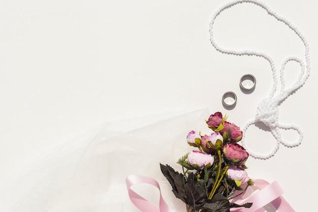 Blumenstrauß von rosen nahe bei hochzeitseinzelteilen mit kopienraum