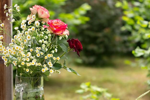 Blumenstrauß von rosen und von gänseblümchen in der gartengrußkarte