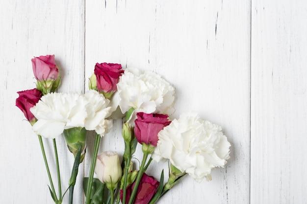 Blumenstrauß von rosen und von gartennelken auf hölzernem weißem backgeound