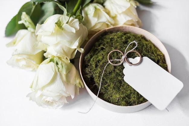 Blumenstrauß von rosen und von schüssel moos und von eheringen mit leerem tag