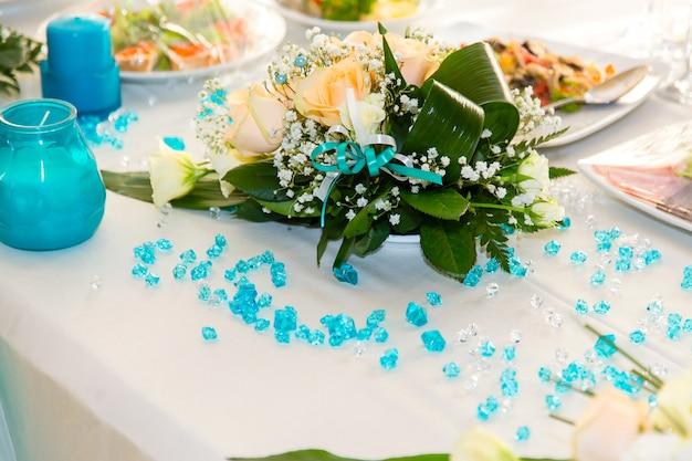 Blumenstrauß von rosen und von türkisdekoration auf der hochzeitstafel