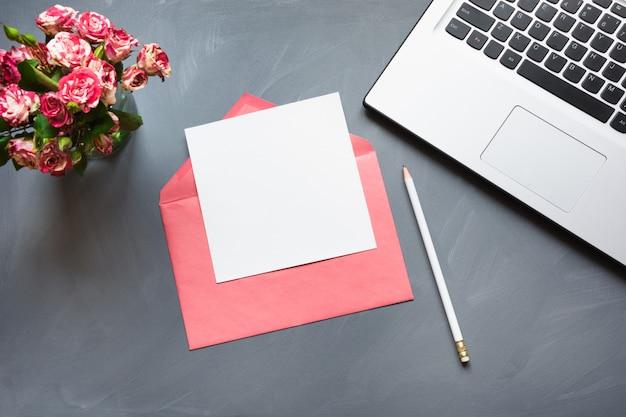Blumenstrauß von rosen, von umschlag mit blatt und von laptop auf grau. valentinstagskarte.