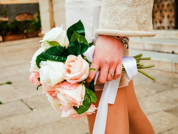 Blumenstrauß von rosenblumen in den händen der modernen hippie-braut. modernes minimalismushochzeitskonzept. städtischer hintergrund